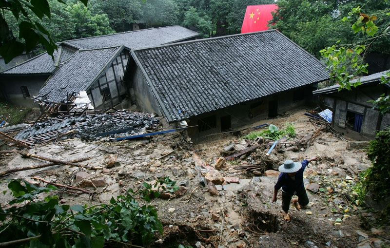 A worker passes buildings destroyed by mudflows at the memorial site of Zhazidong Prison on July 19, 2007 in Chongqing Municipality, China. (China Photos/Getty Images)