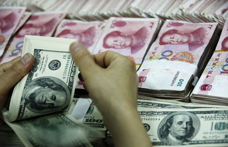 A bank clerk counts a stack of US dollars together with stacks of 100 yuan notes at a bank in Huaibei, China on May 20, 2010. (AFP/AFP/Getty Images)