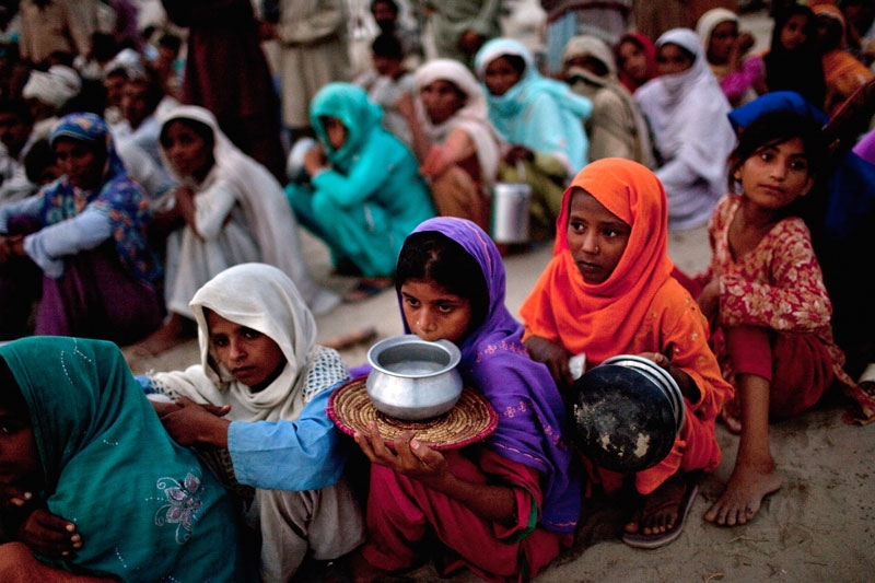 Villagers, displaced from their homes by flooding, hold empty containers as they queue for soup and relief rations on August 25, 2010 in the Sultan Colony Army flood relief camp near Muzaffargarh in Punjab, Pakistan. (Daniel Berehulak/Getty Images)