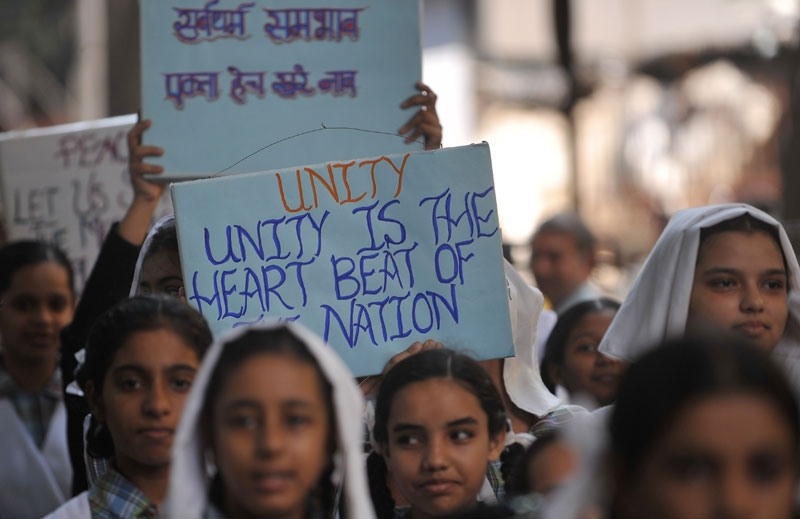 In Mumbai on Sept. 29, 2010, Indian schoolgirls hold signs advocating for tolerance as they march with a peace rally on the eve of the Babri Masjid mosque verdict. (Punit Paranjpe/AFP/Getty Images)