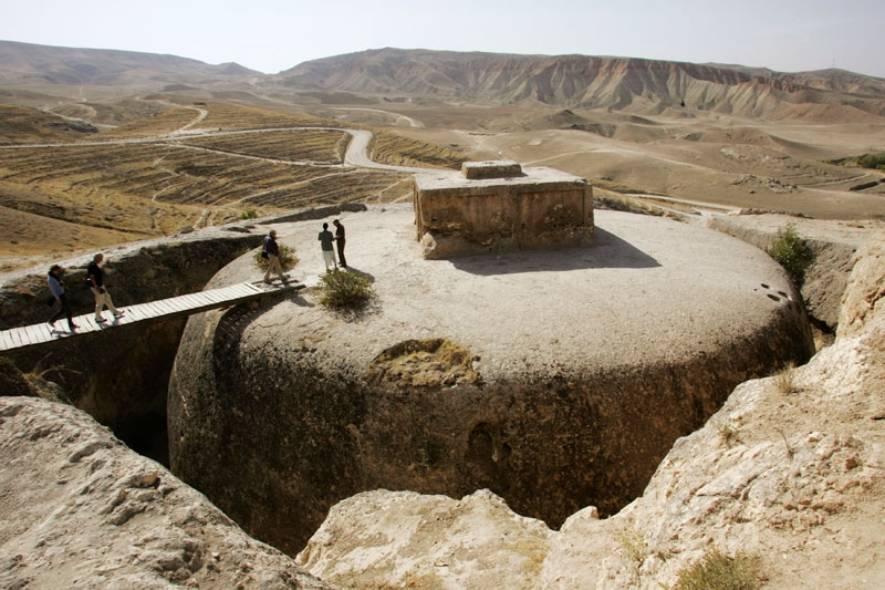 Members of a French archaeological team walk on top of a giant 4th century Buddhist stupa cut into a mountain in Samangan province, Afghanistan, in 2006. A similar historic site to the south and east in Mes Aynak is now at risk from a copper mine. (John Moore/Getty Images)