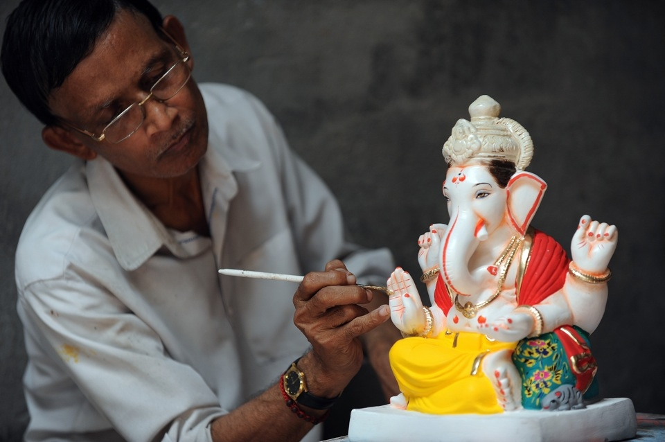 An artist gives finishing touches to a plaster cast idol of Lord Ganesh at a workshop in Pen village in Maharashtra on August 15, 2010. (Indranil Mukherjee/AFP/Getty Images)