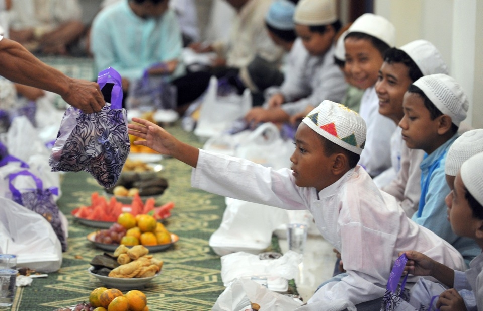 Indonesian children from poor families receive a bag of gifts before they partake in an Iftar or breaking of the fast with fruits, rice cakes, water, and juice at Darussalam mosque in central Jakarta on September 5, 2010. (Romeo Gacad/AFP/Getty Images)