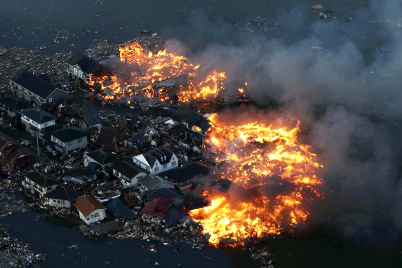 Fire and water engulf homes after an 8.9-magnitude earthquake triggered a tsunami at Natori city in Miyagi prefecture, northern Japan on March 11, 2011. (STR/AFP/Getty Images)