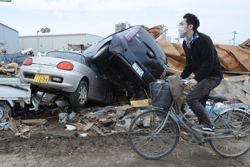 A man cycles past upturned cars and tsunami wrought devastation in Natori City, Miyagi prefecture on March 14, 2011. (Mike Clarke /AFP/Getty Images)
