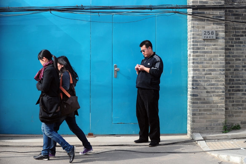 Pedestrians walk past a plainclothes policeman (R) standing in front of the entrance to the studio of outspoken Chinese artist Ai Weiwei in Beijing on April 8, 2011. (Frederic J. Brown/AFP/Getty Images)