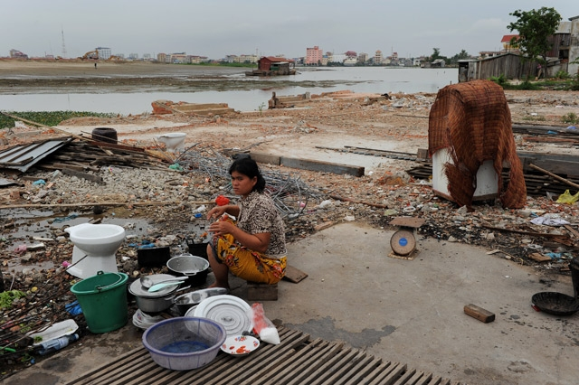 A Cambodian woman washing dishes outside her house on the edge of the Boeung Kak lake (background) in central Phnom Penh as debris from destroyed buildings litter the ground nearby on May 25, 2011. (Christophe Archambault/AFP/Getty Images)