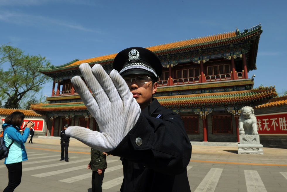 A Chinese policeman blocks photos from being taken outside Zhongnanhai, central headquarters for China's Communist Party, after the sacking of politician Bo Xilai from the country's powerful Politburo, in Beijing on April 11, 2012. (Mark Ralston/AFP/Getty Images)