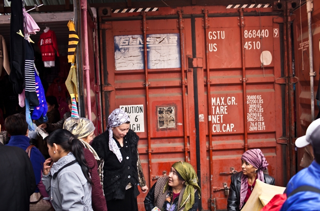 A group of Kyrgyz female traders chat and laugh in front of storage containers that are often used as storefronts in bazaars across Kyrgyzstan.  (Sue Anne Tay)