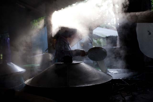 A cook shrouded in steam inside a rice noodle factory. (Hélène Franchineau)