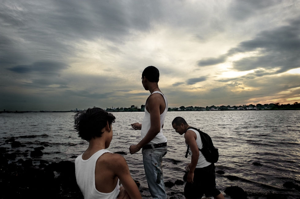 From left to right, Joshua Vatthanavong, 11, Joey Vatthanavong, 16, and Sanet Kek, 28, fish without poles at Ferry Point Park in The Bronx, N.Y. (Pete Pin)