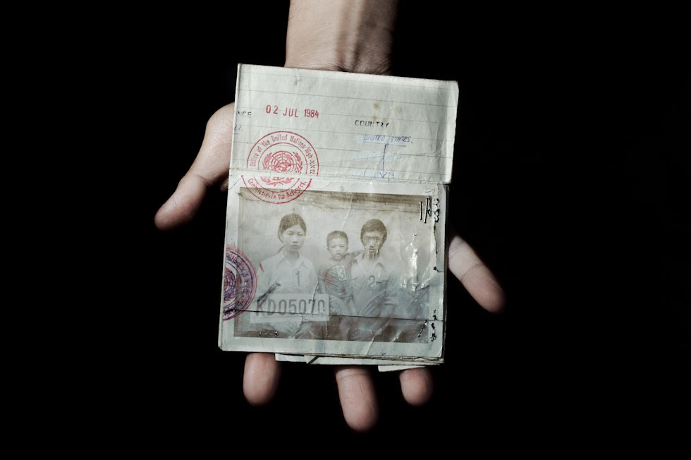Sonny Vaahn, 25, holds his family members' refugee ID card, given upon initial entry into a refugee camp along the Thai-Cambodian border. (Pete Pin)