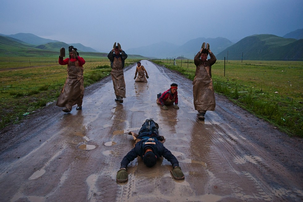 Pilgrims proceed at a snail's pace performing the Chak Tsal, the Tibetan name for ritual prostration (see slide #3). Their journey from Qinghai will take six months, along the northern branch of the Tea Horse Road to the sacred city of Lhasa. (Michael Yamashita)