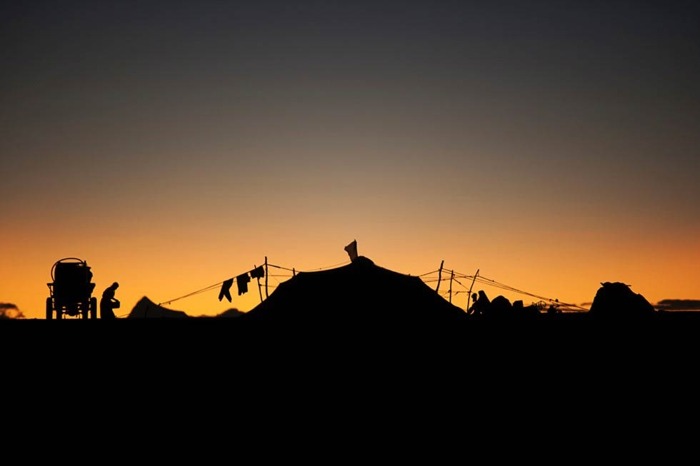 Silhouetted against the morning sunrise, a nomad encampment is situated along Route 109, near Namtso Lake. (Michael Yamashita)
