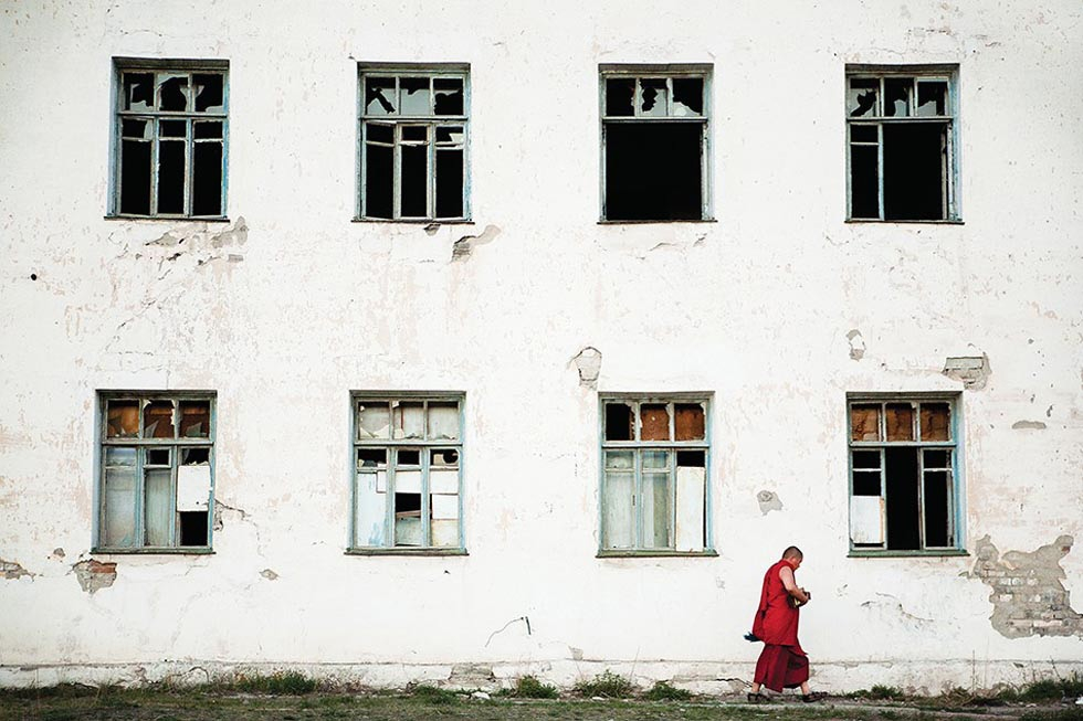 A monk walks past an abandoned Soviet-era building on the outskirts of Ulaanbaatar. (Taylor Weidman)