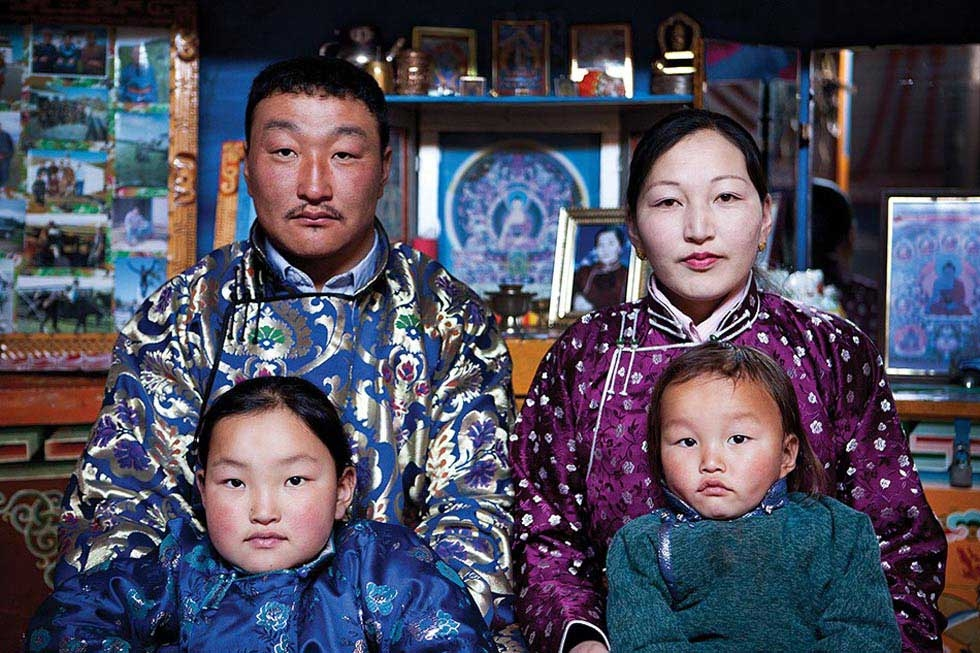 A herding family, dressed in their finest feel (robes), pose for a portrait in front of their family altar. (Taylor Weidman)