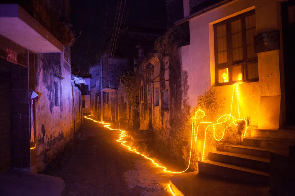 A string of LED lights designed for the Harvestival by Taiwanese architect Teng Hai lit the alleyways of Bishan, providing the village with its first street light. The light remained on for three days before it was ordered turned off. (Leah Thompson)