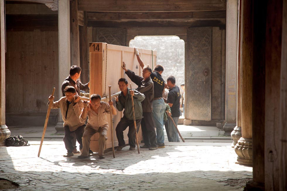 Ten local villagers work with employees of Huaxie International Fine Art to load crates of photographs into Guanyu Tang ancestral hall in Pingshan Village in preparation for the Coal+Ice exhibition. (Leah Thompson)