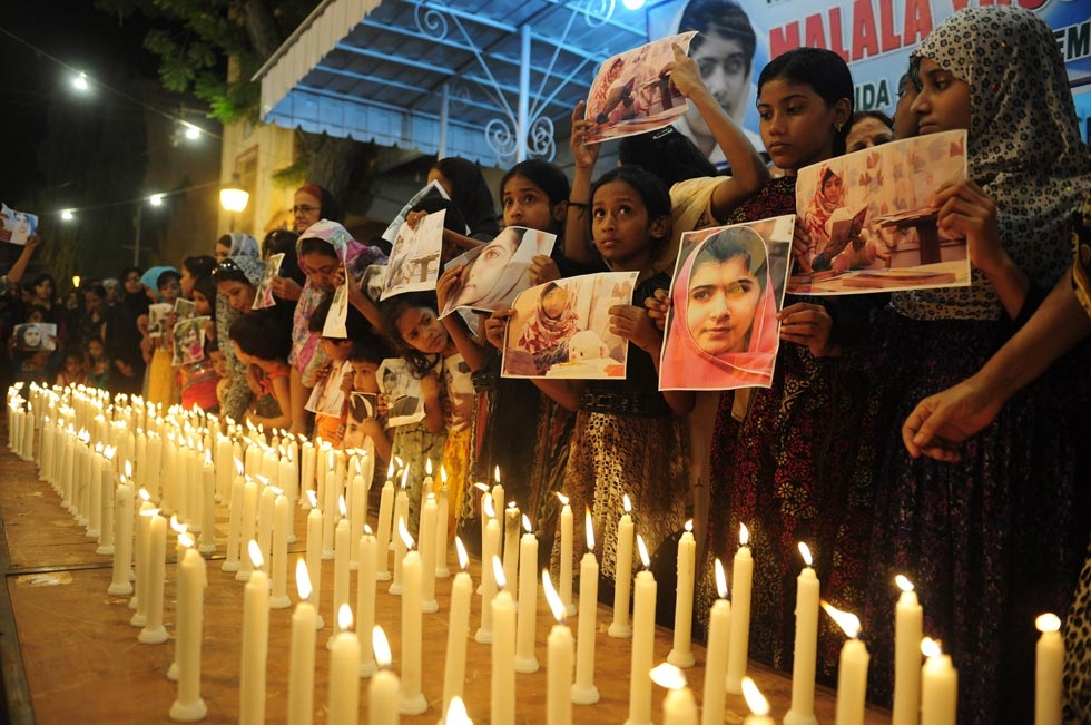"Malala Yousufzai, a 15-year-old Pakistani activist, was shot by the Taliban on October 9, 2012 for promoting girls' education. Her supporters held her photographs as they stood alongside burning candles at a ceremony to mark ""Malala Day"" in Karachi on November 10, 2012. (Rizwan Tabassum/AFP/Getty Images)"