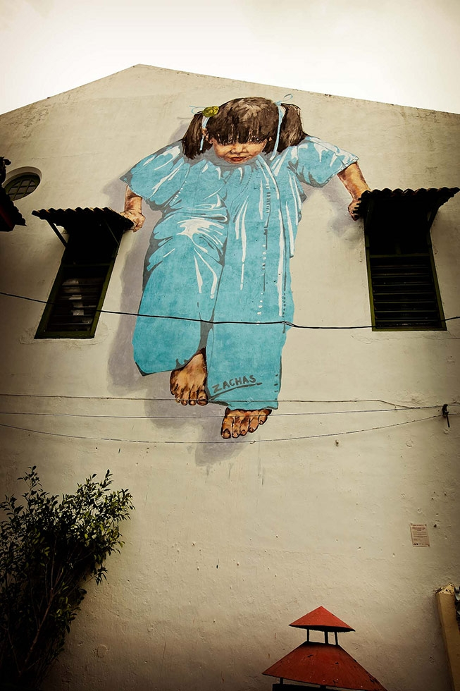 """Girl in Blue,"" a large Zacharevic mural in George Town, Penang. (Catherine Mar)"