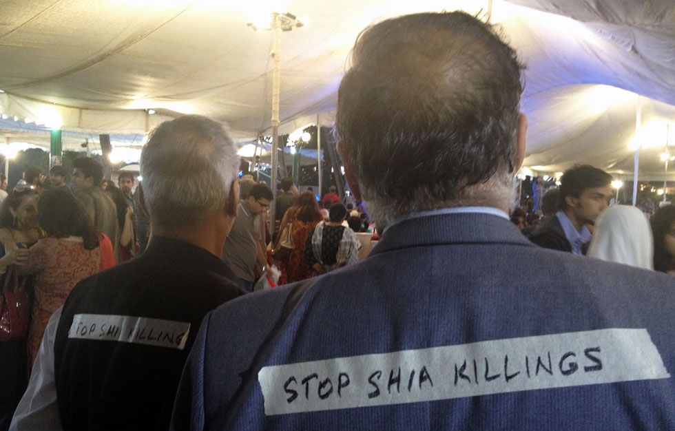 "Attendees wearing signs that read ""Stop Shia Killings"" were a reminder of the troubles impinging on the Festival. (Annie Ali Khan)"