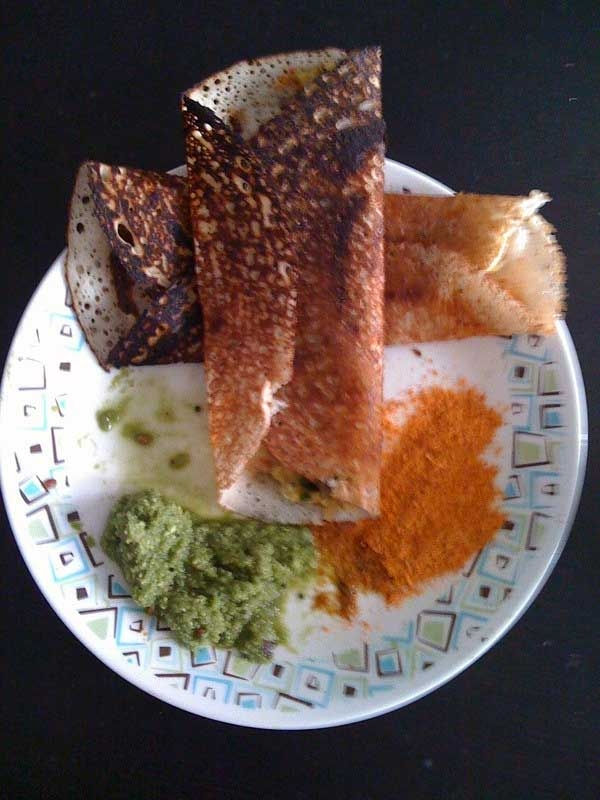 Dosa with green homemade coconut chutney and chutney pudi. (piyoo/Flickr)