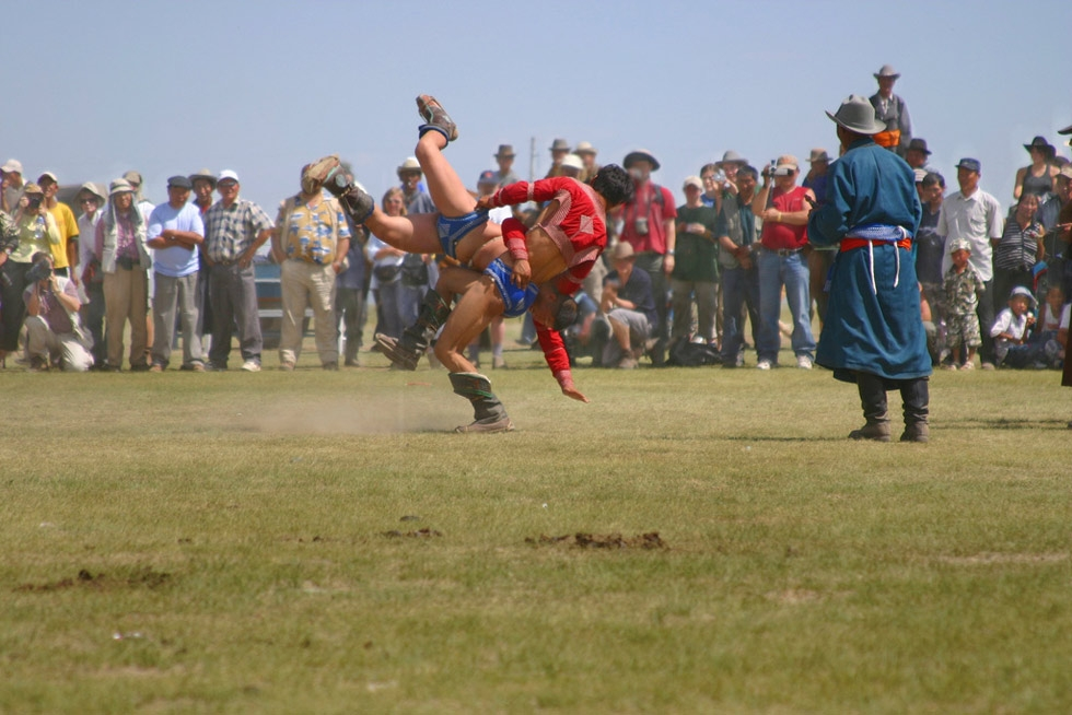 A wrestling match occurs in an open field as part of the Naadam festival. (Emilia Tjernström/Flickr)