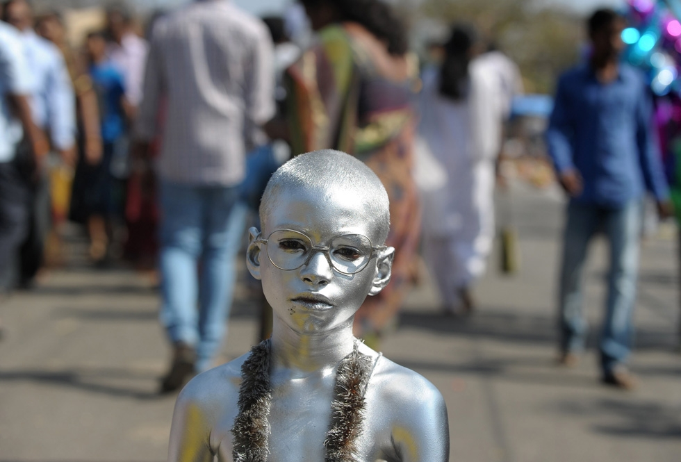 An Indian boy dressed as Mahatma Gandhi begs for alms from Hindu devotees during the Maha Shivaratri festival in Hyderabad, India on February 27, 2014. (Noah Seelam/AFP/Getty Images)