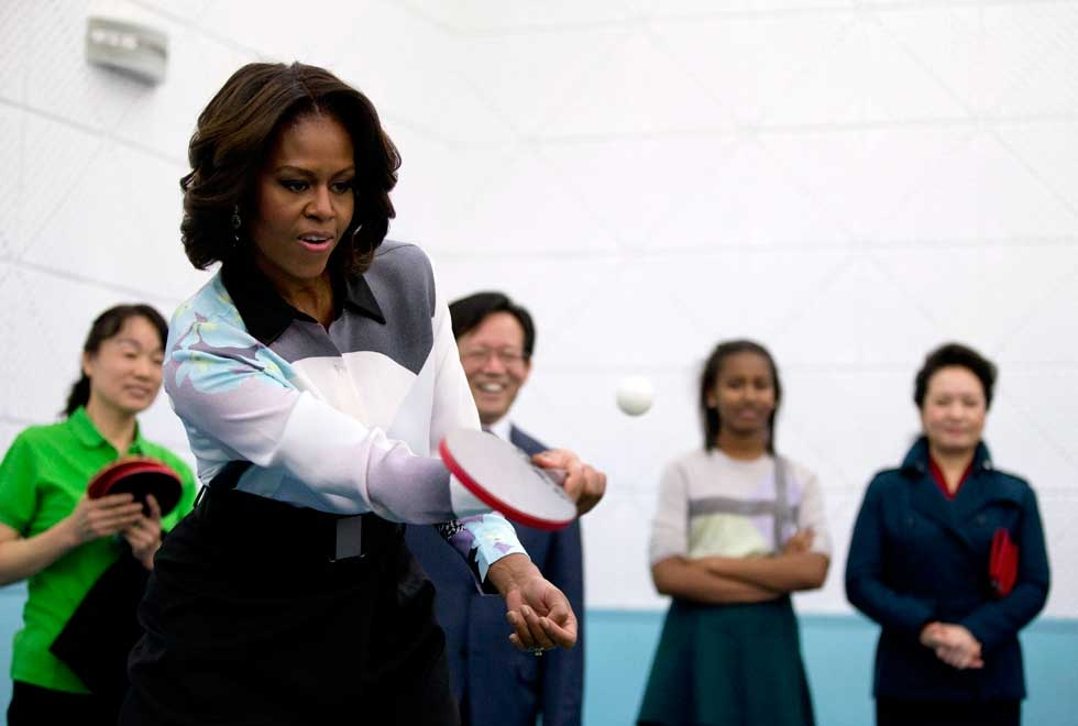 Michelle Obama plays table tennis as Peng Liyuan, wife of Chinese President Xi Jinping (R), looks on during their visit to the Beijing Normal School on March 21, 2014. (Andy Wong-Pool/Getty Images)