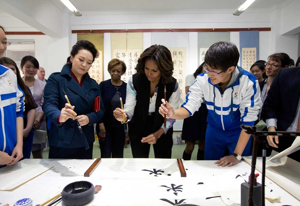 Peng Liyuan, wife of Chinese President Xi Jinping (L), shows U.S. First Lady Michelle Obama (C) how to wield a writing brush as they visit a traditional calligraphy class at the Beijing Normal School on March 21, 2014. (Andy Wong-Pool/Getty Images)