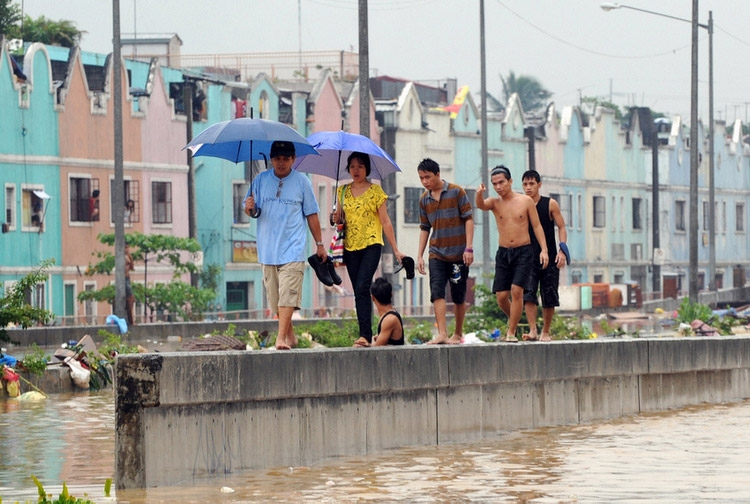Pedestrians in Manila negotiate a flooded street. (Ted Aljibe/AFP/Getty)