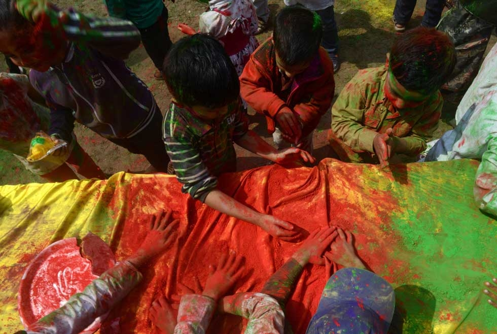 Children play with gulal as they celebrate Holi in Siliguri, India on March 4, 2015. (Diptendu Dutta/AFP/Getty Images)