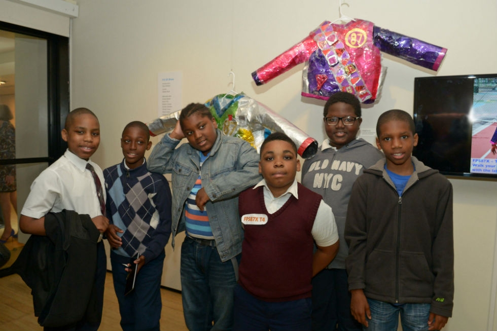 Student artists pose in the gallery in front of Futuristic Prototype Suit 87 – Type 1, 2, 3, & 4. (Elsa Ruiz)