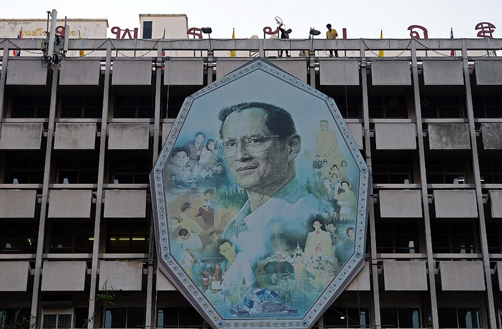 Workers use ropes to remove a portrait of King Bhumibol Adulyadej and install a new one on a facade as people gather at the Siriraj hospital where the King has been staying for months on the eve of his 88th birthday in Bangkok on December 4, 2015. (Christophe Archambault/AFP/Getty Images)