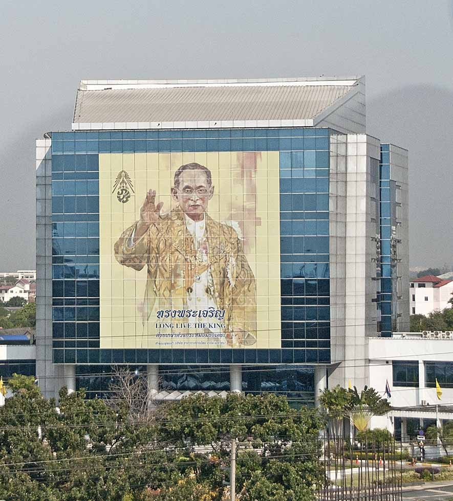 A photo of Thai King Bhumibol Adulyadej graces the side of a building in Thailand. (Marshall Segal/Flickr)