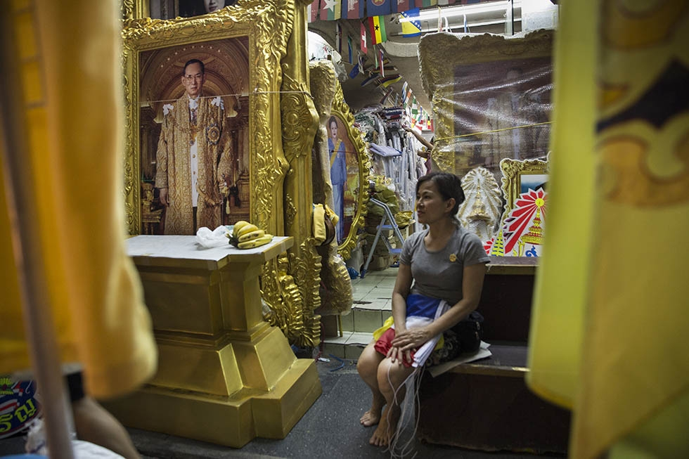 A woman waits for customers that want to buy flags and paintings as the celebration for Thailand's King Bhumibol Adulyadej's 88th birthday begins on December 4, 2015 in Bangkok, Thailand. (Paula Bronstein/Getty Images)