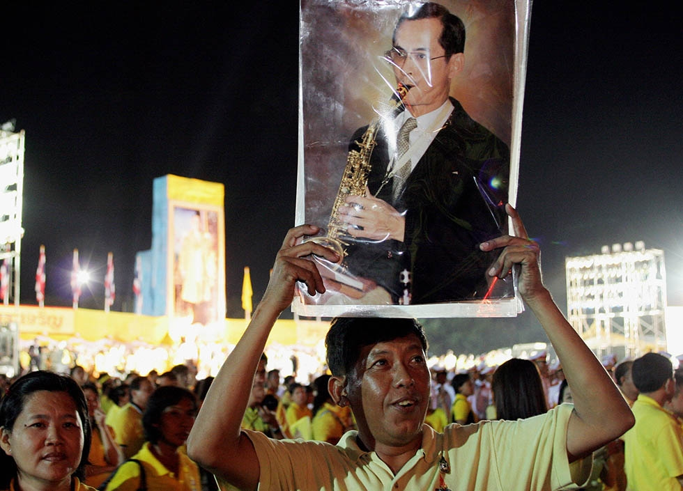 A well-wisher holds a portrait of Thai King Bhumibol Adulyadej to celebrate his 60th anniversary on the throne at Sanum Laung grounds in front of the Grand Palace in Bangkok on June 9, 2006. (Tang Chhin Sothy/AFP/Getty Images)