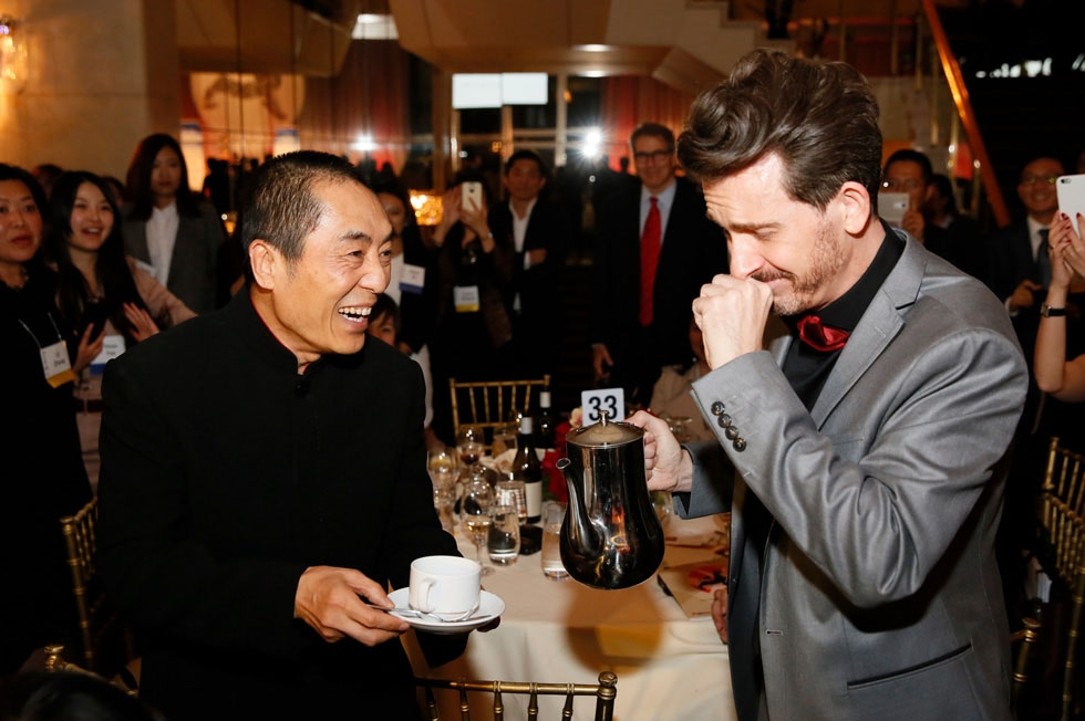 Emcee Jeff Locker (right) fulfills a dream to pour Zhang Yimou, director and Lifetime Achievement Award winner, a cup of coffee during the 2015 Asia Society U.S.-China Film Summit and Gala held at the Dorthy Chandler Pavilion in Los Angeles on November 5, 2015. (Ryan Miller/Capture Imaging)
