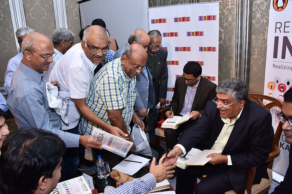 Nandan Nilekani, former chairman of the Unique Identification Authority of India (UIDAI) and co-founder of Infosys, and Viral Shah, founding partner of Julia Computing, sign books after a conversation at Asia Society's India Center in Mumbai on November 7, 2015. (Liberty Event Management/Asia Society)