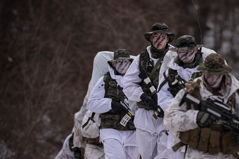 South Korean and U.S. soldiers walk in the snow during a joint annual winter exercise in Pyeongchang, South Korea on January 28, 2016. (Ed Jones/AFP/Getty)