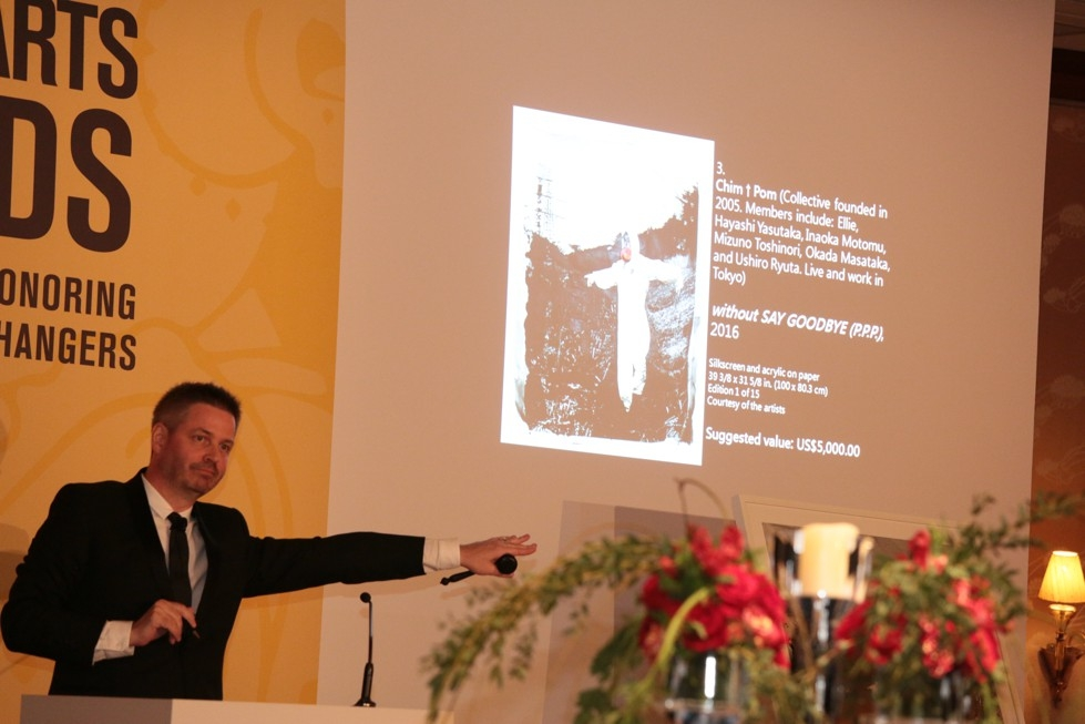 2016 Asia Arts Awards auctioneer Ian McGinlay, Senior Director of Asia & Head of Client Development at Sotheby's, offers a print by ChimPom during the live auction.