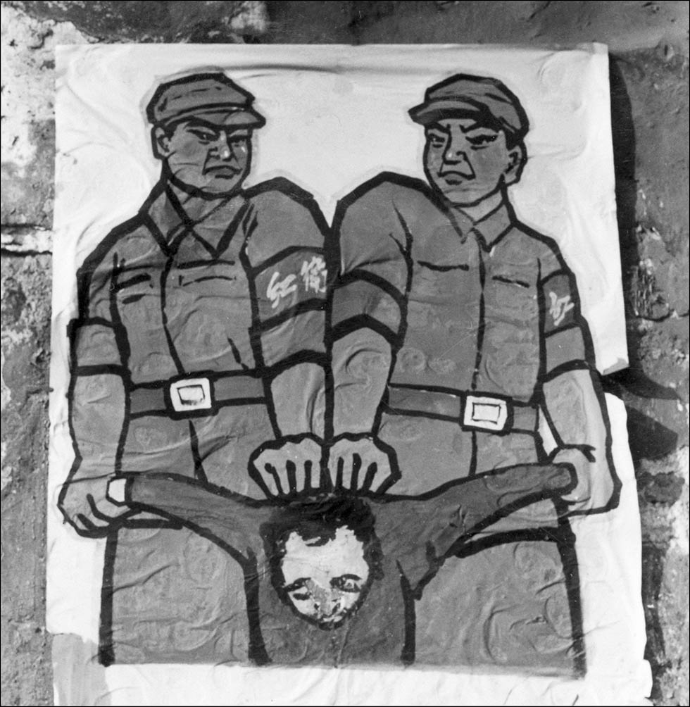 "A poster is displayed in late 1966 in Beijing features how to deal with a so-called ""enemy of the people."" (Jean Vincent/AFP/Getty Images)"