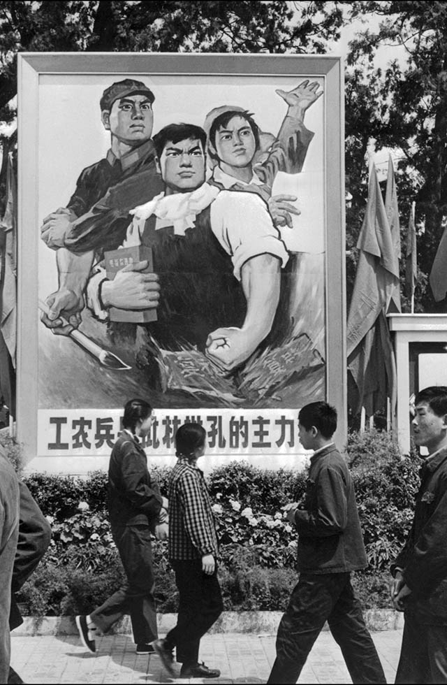 "In May 1974, Beijing residents pass by a poster saying ""Peasants and soldiers are the principal force in the fight against Lin Biao and Confucius."" Once Mao's designated successor, Lin was purged in 1971 and killed in a plane crash, apparently while attempting to flee to the Soviet Union after an attempted coup against Mao. (AFP/Getty Images)"