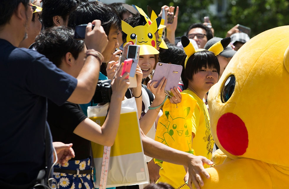 People take photographs of performers dressed as Pikachu, marching during the Pikachu Outbreak event on August 7, 2016 in Yokohama, Japan. (Tomohiro Ohsumi/Getty Images)