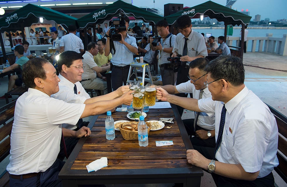 Choe Yong Nam (L), director of the General Bureau of Public Service who doubles as chairman of the preparatory committee for the festival, says 'cheers' with other officials after the opening ceremony of the Pyongyang Taedonggang Beer Festival on August 12, 2016. (Kim Won-jin/AFP/Getty Images)