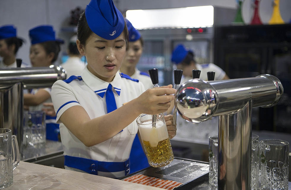 A waitress draws jugs of beer to serve before the opening of the Pyongyang Taedonggang Beer Festival. (Kim Won-jin/AFP/Getty Images)