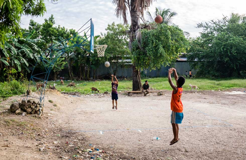 Two children quickly run on the court to shoot a few hoops while the adults are in action at the other end. Cebu, Philippines. (Richard James Daniels)