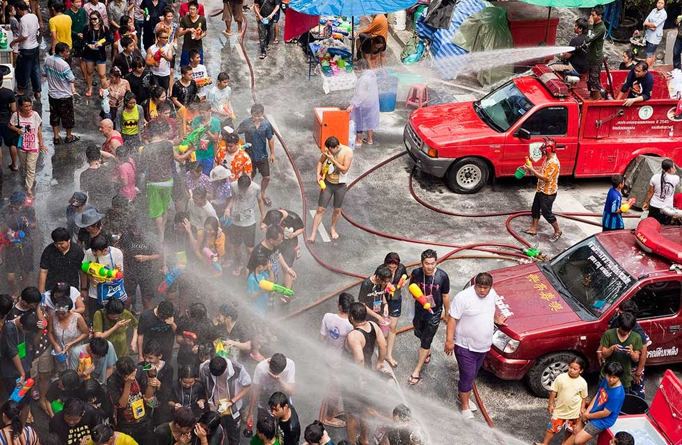 Thai fire fighters soak the crowd with their fire hoses during a community water fight on Silom Road as part of the Songkran water festival on April 14, 2013 in Bangkok, Thailand. (Jack Kurtz/Getty Images)