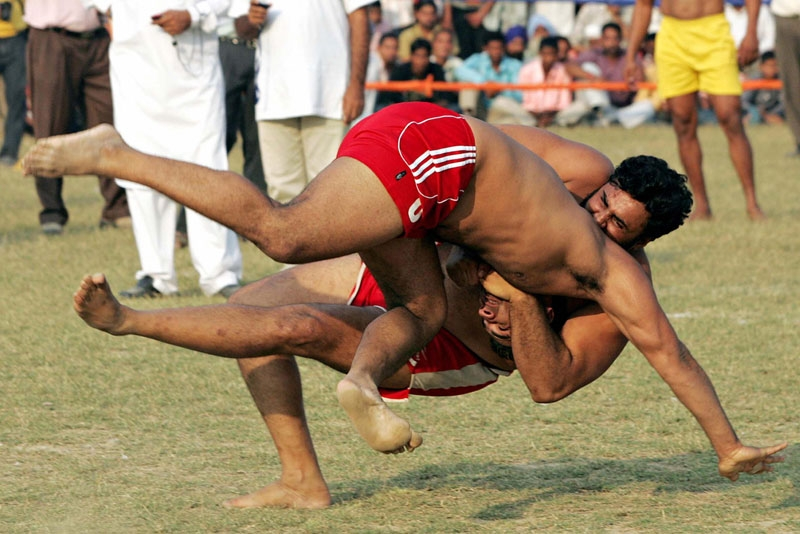 An Indian kabbadi player (L) is brought to the ground during the 2008 Sri Guru Gobind Singh Kabaddi Series in Gopalpur Majwind village, some 25 kms from Amritsar on November 9, 2008. (Narinder Nanu/AFP/Getty Images)