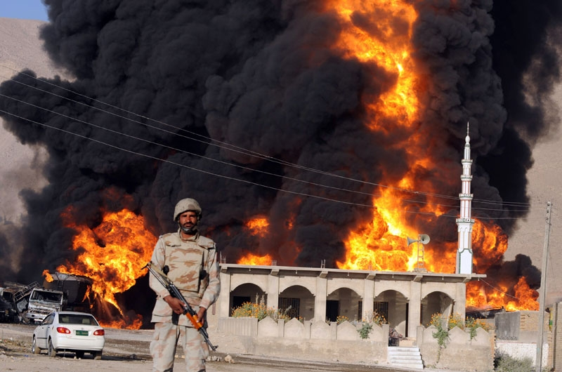 A Pakistani paramilitary soldier stands guard in front of burning NATO supplies oil tankers following a gunmen attack in Quetta on October 6, 2010. (Banaras Khan/AFP/Getty Images)